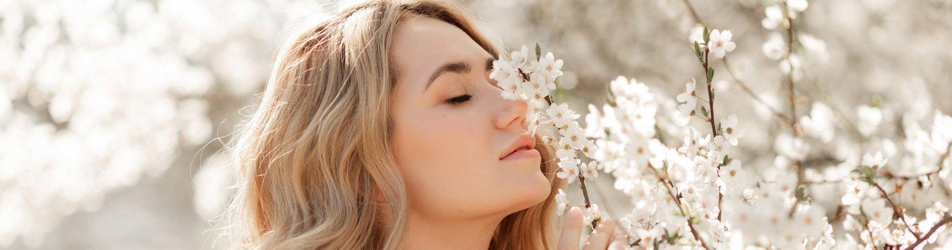 Frau riecht an frischen Blüten eines Baums